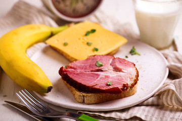 Cheese and ham sandwiches and  milk.Healthy breakfast.