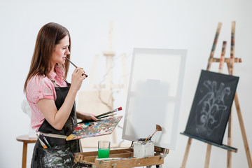 A young woman painter in a bright white studio draws a picture on canvas on an easel.