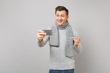Joyful young man in gray sweater, scarf holding thermometer, doing selfie shot on mobile phone, making video call isolated on grey background. Health ill sick disease treatment, cold season concept.