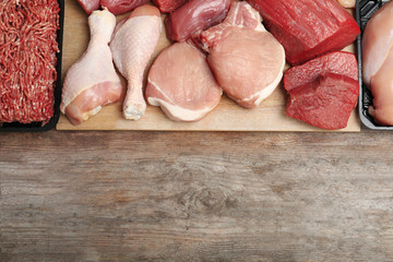 Flat lay composition with fresh raw meat and space for text on wooden background