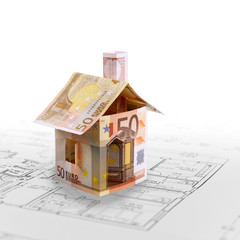 House from banknotes on building plan