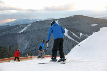 People skiing on snowy hill in mountains. Winter vacation