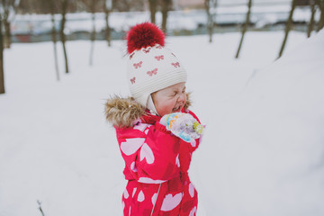 Funny little girl in winter warm clothes and hat having fun and making snowball in snowy park or forest outdoors. Winter fun, leisure on holidays. Love relationship family childhood lifestyle concept.