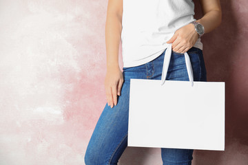 Woman holding mock-up of paper shopping bag on color background, space for text