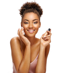 Happy woman applying tone cream on her face. Photo of african american woman on white background. Skin care and beauty concept