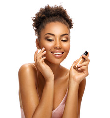 Charming young girl applying tone cream on her face. Photo of smiling african american girl on white background. Skin care and beauty concept
