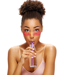 Young girl with pink eye patches on her face and drinks clean water. Photo of african american girl isolated on white background. Youth and Beauty