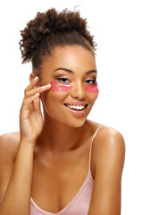 Laughing girl with pink eye patches on her face. Photo of african american girl touching her smooth skin on white background. Skin care concept