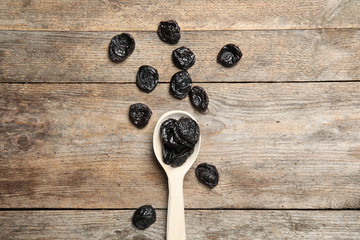 Spoon of dried plums on wooden background, top view. Healthy fruit