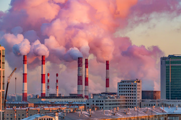 Steam or smoke comes from the pipes. Combined heat and power plant in the city. Landscape at sunset or dawn.