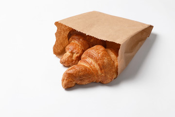 Paper bag with delicious croissants on white background