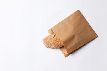 Paper bag with bread on white background, top view. Space for text