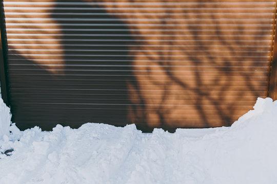 Snow drifts on brown metal garage doors background. Winter urban city season.