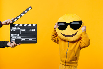 Little kid boy 3-4 years old in yellow clothes isolated on orange wall background, children studio portrait. People childhood lifestyle concept. Hand hold film making clapperboard. Mock up copy space.