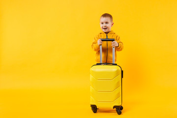 Wall Mural - Little traveler tourist kid boy 3-4 years old isolated on yellow orange wall background studio. Passenger traveling abroad to travel on weekends getaway. Air flight journey concept. Mock up copy space
