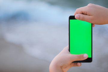 Young boy holding black smartphone in hands with blank empty green screen while standing at beach of resort. Kid watching something at mobile cellphone with chroma key screen background.