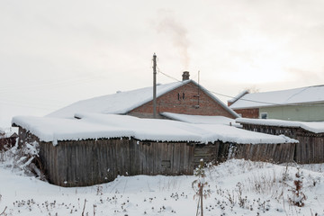 House in a Russian village in the winter, in the snow, with old shabby wooden barns in the foreground