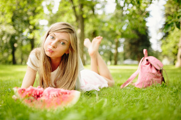 Positive and cute blond girl posing at the park