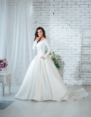 Portrait of beautiful bride woman in gorgeous white wedding dress posing in the bright studio with wedding decoration.