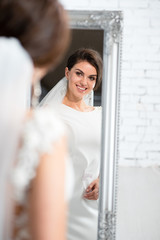 Attractive bride woman with beautiful make up in gorgeous wedding dress looking in the mirror in the bright studio