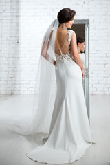 Back view of bride wearing gorgeous luxurious wedding dress with long loop in the bright studio.