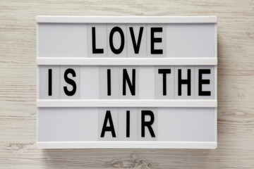 Lightbox with text 'Love is in the air' on a white wooden background. Valentine's Day 14 February.