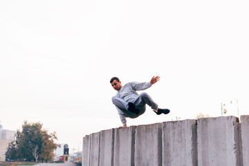 Caucasian man trains parkour while jumping over a high top.