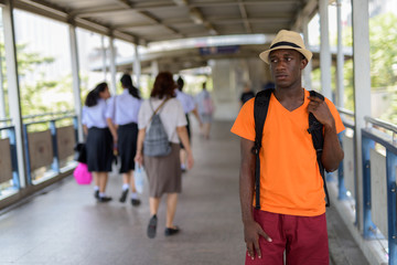 Black African tourist man standing and thinking at the footbridge