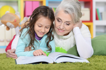 Portrait of grandmother reading book with granddaughter