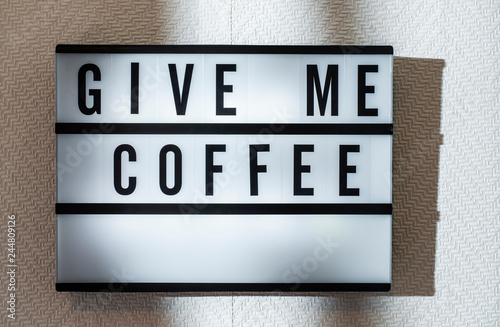 Message Give Me Coffee on illuminated board  Coffee drinking
