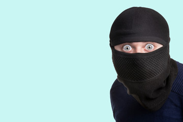 man in a balaclava on a blue background, concept of catching a criminal at a crime scene - fototapety na wymiar