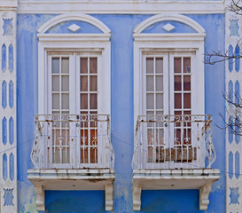 Two windows in bue facade of an old house