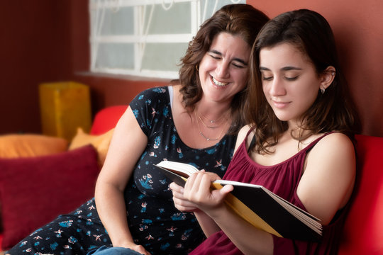 Hispanic teenage girl and her mom reading a book at home