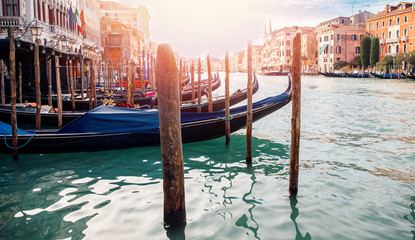 Wooden pole for tying boat close up in center of frameblue-green water Venice, Italian cityscape...