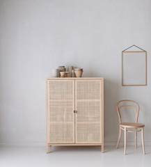 Raum mit Schrank und Stuhl und leerem Bilderrahmen