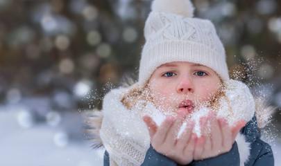 Kind pustet Schnee wie Wunschstaub von den Händen, im Hintergrund verschwommener Winterbokeh