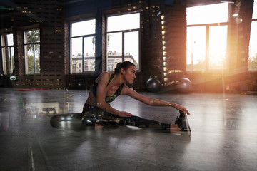 Athletic girl does stretching exercises at the gym. Double exposure
