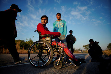 Paraplegic migrant Jose Serrano, from Honduras, rests beside his friend Jerian, during their journey towards the United States, in Niltepec, Mexico