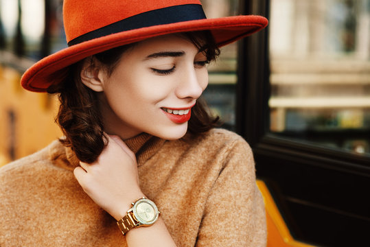 Close up outdoor portrait of young fashionable happy smiling woman wearing golden wrist watch, orange hat, beige turtleneck sweater. Copy, empty space for text