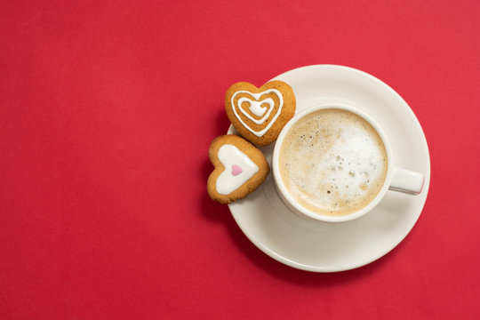 Love, Valentine's Day concept. Cup of coffee or latte and heart shaped cookies, biscuits. Red background, copy space.
