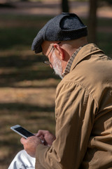 Old man sitting on the bench, with a smartphone
