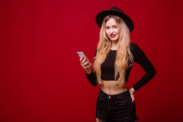 Young blonde woman in fluppy black hat and black clothes use the phone isolated on red background