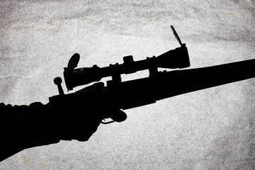 Silhouette of a military carbine on a stone background. Arms in the male hand. Shotgun for long range shooting.