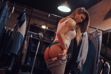 Sexy girl seductively pulling up pants in a fitting room of a clothing store