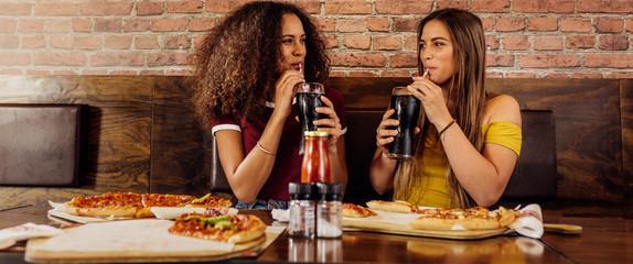 Fototapeta Best friends enjoying drinking cola at cafe