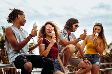 Smiling young friends eating ice-cream outdoors