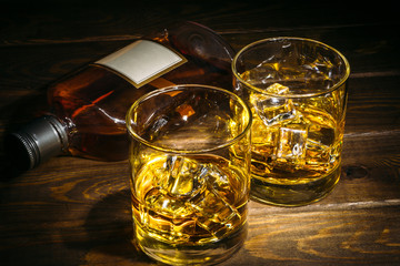 Two glasses of scotch whiskey or cognac with ice cubes and bottle of alcohol liquor on dark wooden background