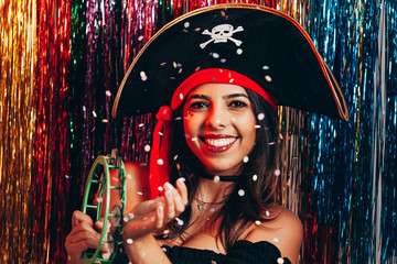 Beautiful young woman having fun with a fake party pirate costume. Brazilian Carnival concept Wall mural