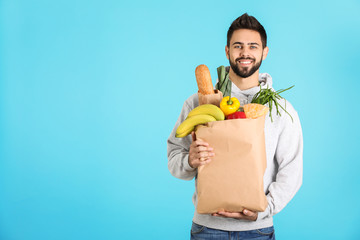 Man holding paper bag with fresh products on color background, space for text. Food delivery service