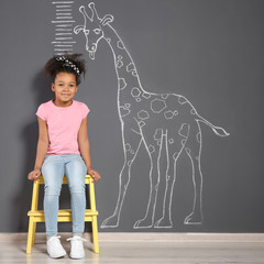 African-American child near grey wall with chalk giraffe drawing and height meter